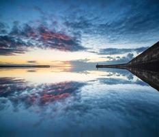 vacker vibrerande soluppgångshimmel över lugna vattenhav med fyren foto