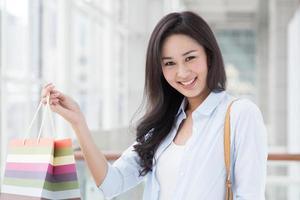 smiley ung asiatisk kvinna med en shoppingväska foto