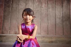 liten flicka i en rosa festklänning som poserar utanför för ett foto