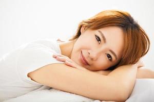 attraktiv ung vacker kvinna som vaknar upp i sängen foto