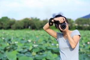 ung kvinna fotograf tar foto utomhus