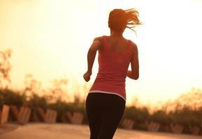 kvinna går för en morgonkörning vid soluppgången foto