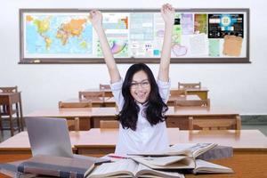 glad tonårsflicka tillbaka till skolan och höja handen foto