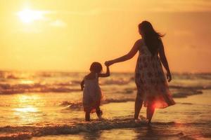 mamma med sin dotter på stranden foto
