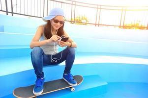 kvinna skateboarder lyssnar musik foto