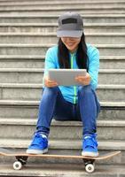 ung kvinna skateboarder använder sin digitala tablett sitter på trappan foto