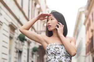 vacker asiatisk kvinna prata med mobiltelefon våren urban utomhus foto