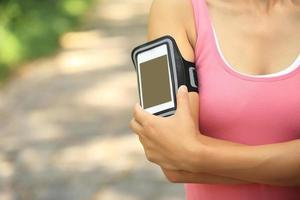 kvinna löpare lyssnar på musik från smart telefon mp3-spelare