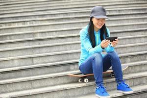 ung kvinna skateboarder använder sin mobiltelefon sitter på trappan foto