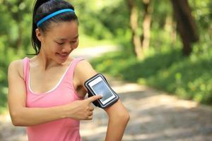 kvinna lyssnar på musik från smart telefon mp3-spelare foto