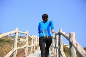 frisk kvinna springer upp på bergstrappor foto
