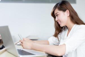 asiatisk vacker kvinnlig studentstudie med surfplatta i klassrummet foto
