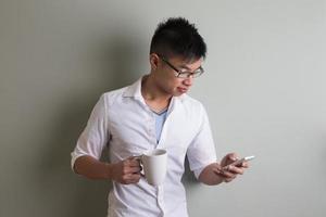 porträtt av en trendig asiatisk man som använder sin mobiltelefon. foto