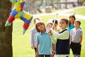 barn som slår pinata på födelsedagsfesten foto