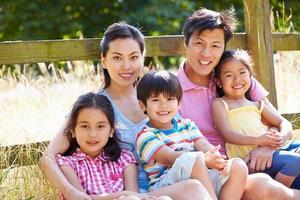asiatisk familj kopplar av vid grinden på promenad på landsbygden foto