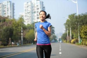 fit sportkvinna som kör på asfaltvägen foto
