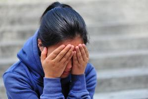 kvinna täcker ansiktet med händerna foto