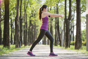 sportig ung asiatisk kvinna som sträcker sig efter jogging i skogen foto