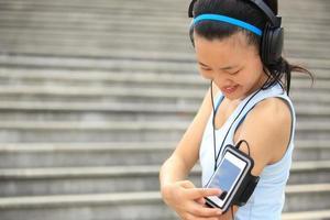 kvinna lyssnar på musik i hörlurar från smart telefon mp3 foto