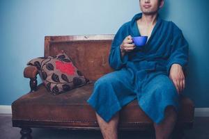 ung man dricker från koppen på vintage soffan foto