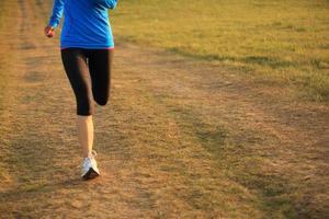 löpare idrottare kör på gräsmark trail foto