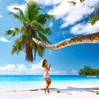 kvinna i blå klänning som svänger på stranden foto
