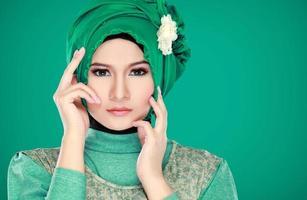 mode porträtt av ung vacker muslimsk kvinna med gröna kostnader foto
