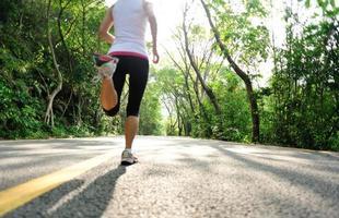 hälsosam livsstil fitness sport kvinna ben kör på skogen väg foto