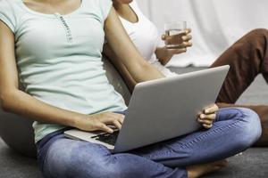 unga kvinnor sitter medan du använder laptop foto