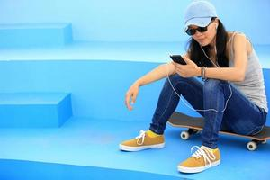 kvinna skateboarder lyssnar musik