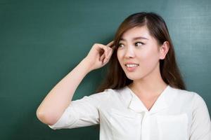 asiatisk vacker kvinna som står framför tavlan med gest