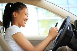 glad kvinna förare använder sin mobiltelefon i bilen foto