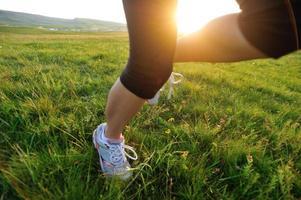 löpare idrottsman ben kör på soligt gräs fält foto