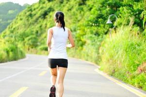 asiatisk kvinnalöpare som kör utomhus på morgonen foto