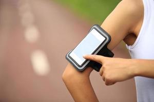 kvinna löpare lyssnar på musik från smart telefon mp3-spelare foto
