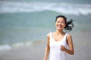 frisk sportkvinna som körs vid stranden foto