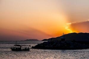 solnedgång med en liten båt