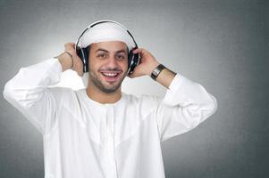 ung glad arabisk man med hörlurar som lyssnar på musik foto