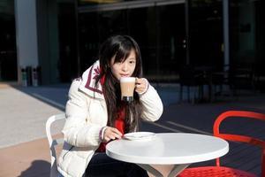 orientalisk flicka som dricker kaffe på utomhuscafé foto