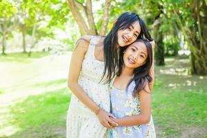 två unga asiatiska systrar i park foto