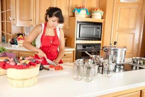 kvinna som konserverar frukt och grönsaker foto
