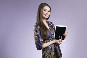 leende kvinna som visar digital tablet foto