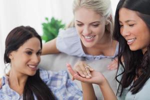 vänner som beundrar brunetter förlovningsring foto