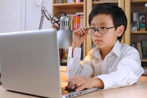 smart asiatisk pojke som bär glasögon framför bärbar dator foto