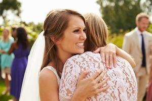 brud som kramar mamma på bröllopsdagen