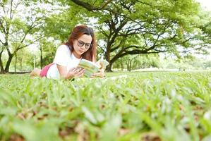 ung kvinna som ligger ner och läser bok i parken foto