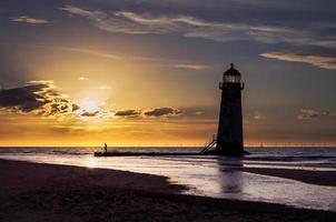 fyr på stranden vid solnedgången foto