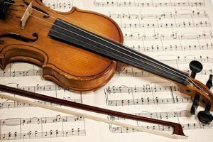 gammal fiol och rosett på musiknoter foto