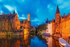 stadsbild med belfort från rozenhoedkaai i Brugge vid solnedgången foto