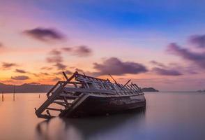 övergiven fiskebåt vid solnedgången, Thailand. foto